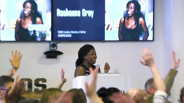 Rayshauna Gray speaking at a podium, audience hands raised